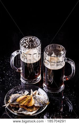 Photo of two mugs of beer with plate of fish on ablack table