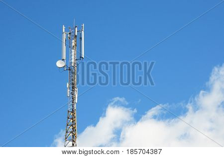 Cellular transmitter on blue sky with clouds background and copy space.