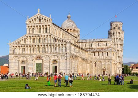 Tourists on the Square of Miracles (Campo dei Miracoli) admire the Duomo and the Leaning Tower (Torre Pendente) in Pisa, Tuscany, Italy - 8 October 2011