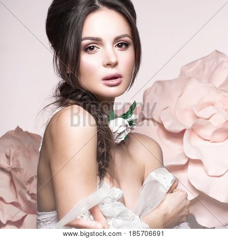 Beautiful girl with classic make-up and hairstyle in delicate Underwear with large flowers on background. beauty face. Photos shot in studio