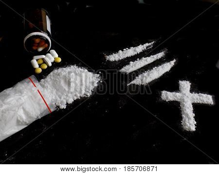 Cocaine drug powder bag, lines and cross and pills on black background