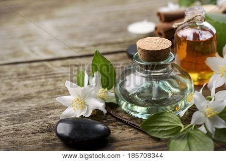 Essential oils with jasmine cinnamon and vanilla on rustic wooden table