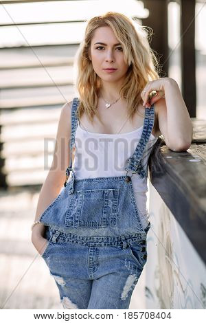 Young Stylish Blonde Girl In Denim Overalls Outdoors With Natural Daylight, A Sunny Day