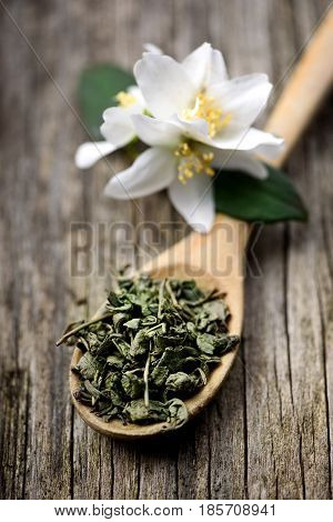 Jasmine and green tea in wooden spoon