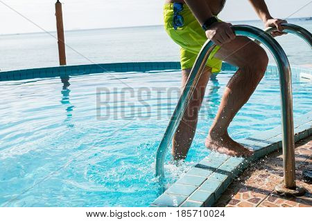 Photo of man in swimming shorts at outdoor pool