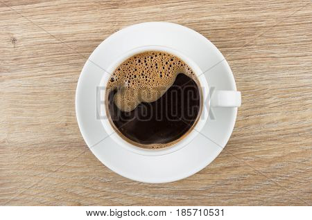 Black Coffee In Cup With Saucer On Wooden Table