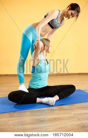 Photo of athlete and trainer practicing yoga in gym