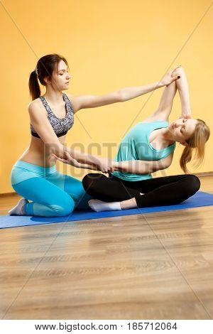 Two young girls doing yoga in gym