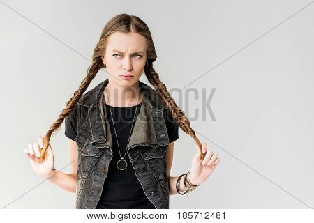 Portrait Of Pensive Rocker Girl With Braids Posing And Looking Away Isolated On Grey