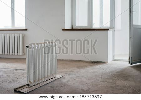 Radiator in the house under construction. The concept of repair in an apartment house. Equipment for the thermal control of an apartment in the interior of a renovated house.