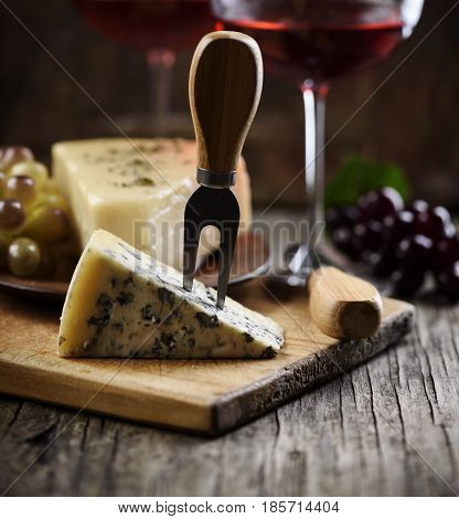 Blue cheese slice and red wine on wooden table.
