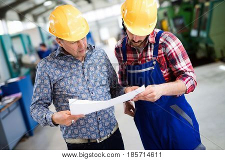 Factory worker discussing data with supervisor in metal industry factory