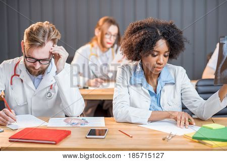 Multi ethnic group of medical students in uniform studying in the modern classroom