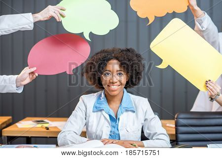 Portrait of an african medical student thinking with colorful clouds sitting at the classroom