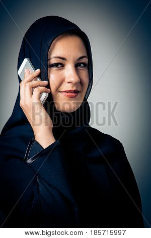 studio shot of young woman wearing traditional arabic clothing, talking on the phone