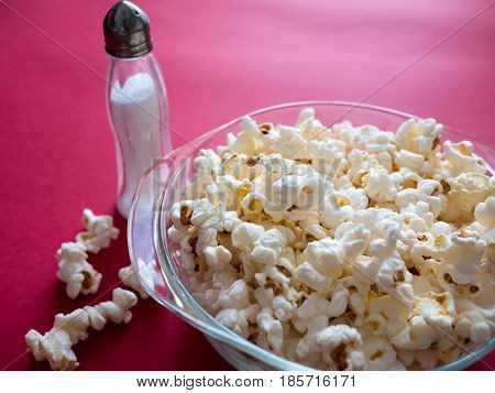 Popcorn In A Bowl With Salt On A Red Background