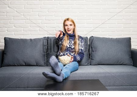 Young Woman Spends His Free Time Watching Tv On The Couch At Home, Munching Popcorn.