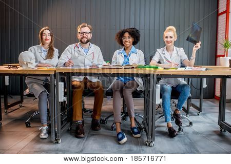 Portrait of multi ethnic group of medical students in uniform sitting in a row together at the desk in the modern classroom