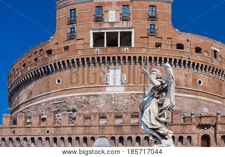 ROME, ITALY - September  13, 2016: Statue of Angel with  a lancer and Castel Sant'Angelo on the background. Ponte Sant'Angelo, Angelo Bridge. Rome. Italy.