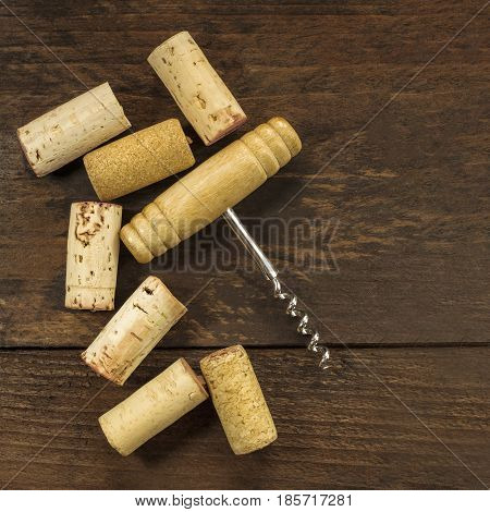 A photo of an old-fashioned corkscrew with corks, shot from above on a dark wooden background texture with copy space. A square design template for a wine list or a tasting invitation