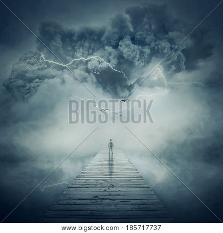 Fantastic view as a man stand on the wooden pier at the middle of the lake in a foggy and stormy day watching a hurricane coming. Facing the life pressure and stress concept.