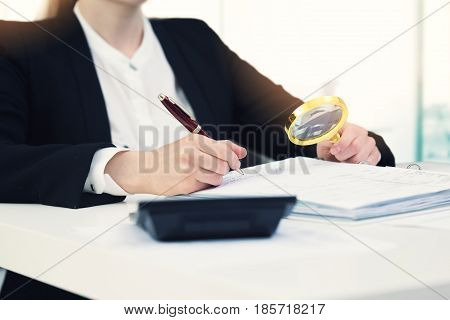 audit concept - auditor with magnifying glass inspecting documents in office