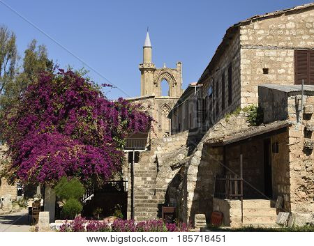 Old house in a church area with a blossom bouganvillea and a blue sky in background picture from the North of Cyprus.