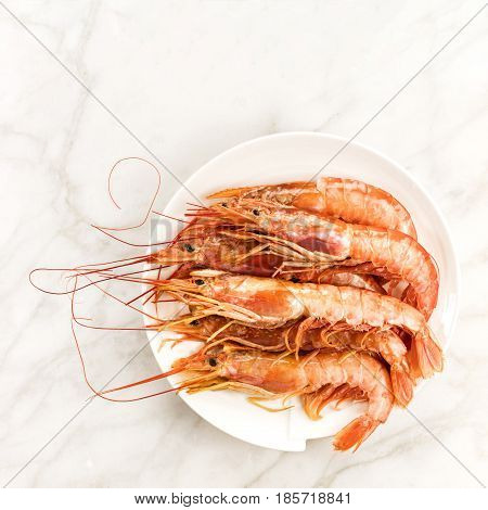 Raw shrimps on a plate, shot from above on a white marble table with a place for text, square photo