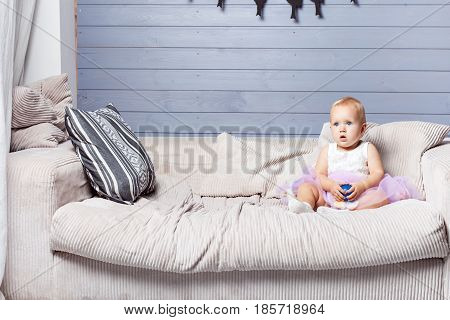 Child girl sitting on the couch and holding a small ball