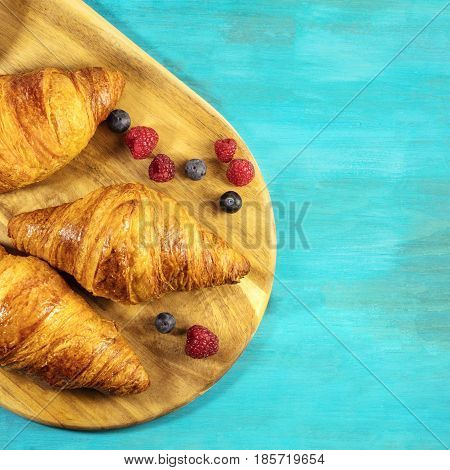 A square overhead shot of crunchy French croissants with fresh raspberries and blueberries on a wooden cutting board and vibrant turquoise texture, with copy space