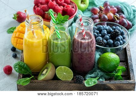 Colorful detox smoothie in bottles with spinach berries mango kiwi lime. Summer diet fresh vegan drink for breakfast or snack.