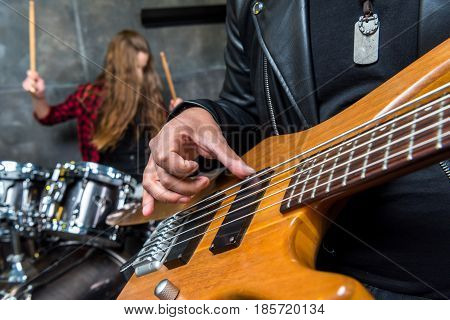 partial view of man playing guitar with woman playing drums behind hard rock music concept