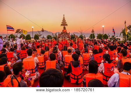 PAYAO THAILAND - FEBRUARY 14, 2014: Buddhists with monks pay respect to Buddha image at Buddh ist temple on island of Payao lake for Buddhist merit event in Payao Thailand