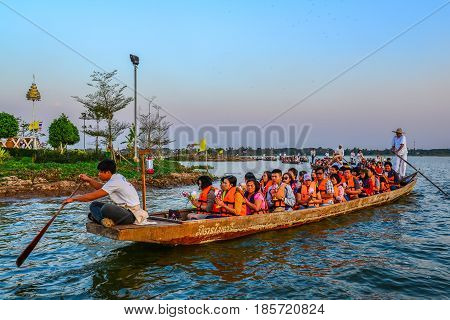 PAYAO THAILAND - FEBRUARY 14, 2014: Buddhists on boats with candles and flowers parade around Buddhist temple on island of Payao lake for Buddhist celebrate event in Payao Thailand