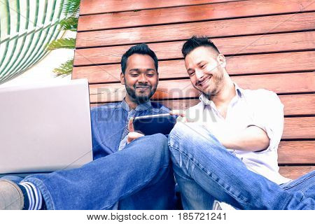 Young interracial couple of happy men using phone sitting on urban wall background - Happy indian and caucasian hipster male looking down at smartphone smiling outdoors