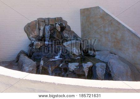 Custom built backyard waterfall sitting against house wall
