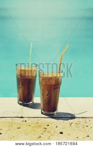 Two glass of iced frappe near the swimming pool. Retro filter image