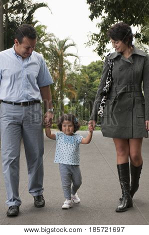 Hispanic parents holding daughter's hands outdoors