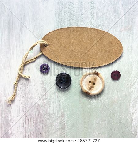 A square photo of a kraft cardboard tag with a piece of twine, with retro buttons, shot from above on a light wooden board texture, with copyspace