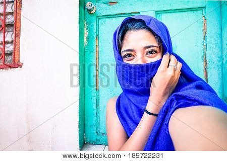 Beautiful filipino muslim woman taking selfie with veiled face outside her house - Young asian girl with deep dark eyes on blue turquoise background - Concept of people different culture and religion