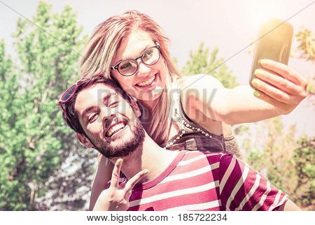 Cheerful couple piggybacki selfie at the park - Playful friends having fun with self photo on sunny summer day - Concept of teenage joy and romantic moment outdoor - Desaturated vintage filter look