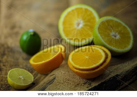 Fresh citrus fruits are placed on a wooden board. From the picture it comes to know how fresh the they are and just by looking you feel fresh as it gives a fresh feeling.