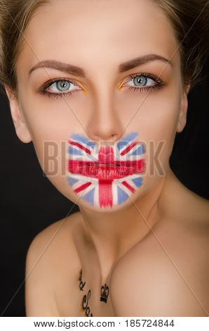 Beautiful woman with english flag on her face black background