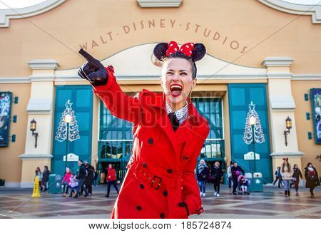 Happy Woman In Front Of Disney Studio 1 Pointing At Something