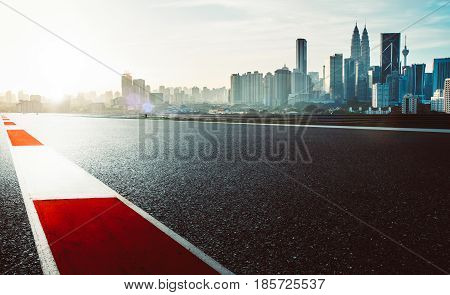 Racetrack with red and white safety sideline modern city background dramatic cloudy sky and vintage mood filter apply .