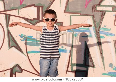 dreaming little boy with sunglasses and sailor vest put his hands to sides portraying the flight
