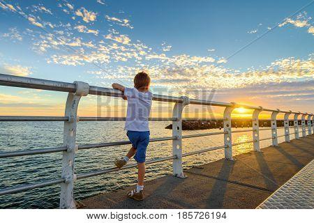 Boy watching sunset from St. Kilda Jetty Melbourne Victoria Australia