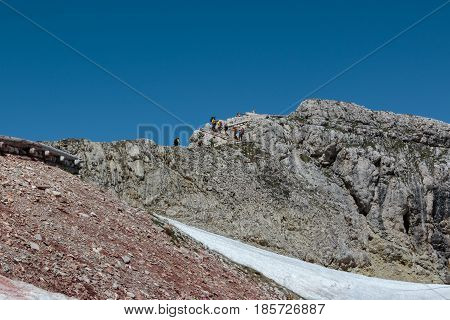 Tourists And Climbers Walking In Stone Path Among Barren Mountains In Italian Dolomites Alps In Summ