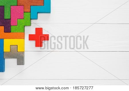 The concept of creative logical thinking. Different colorful shapes wooden blocks on white wooden background flat lay copy space. Geometric shapes in different colors top view. Abstract Background.