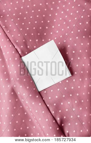 White blank clothes label on pink silk with polka dots closeup